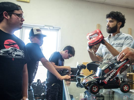 Owners of 3 Crosses RC Racing and Repair Daniel Sanchez, right and Randy Garcia, center, help patrons with their RC cars on Monday, July 2, 2018 at the shop located at 522 E. Idaho Ave. Patrons pictured from left, Dawson Manicki, 19, Cade Martinez, 13, and Jaden Manicki, 13.