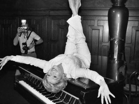 "FILE- In this Sept. 8, 1982, file photo, actress Debbie Reynolds poses on a grand piano at a New York restaurant, as she promotes the revival of the hit musical ""The Unsinkable Molly Brown."" Reynolds, star of the 1952 classic ""Singin' in the Rain"" died Wednesday, Dec. 28, 2016, according to her son Todd Fisher. She was 84."