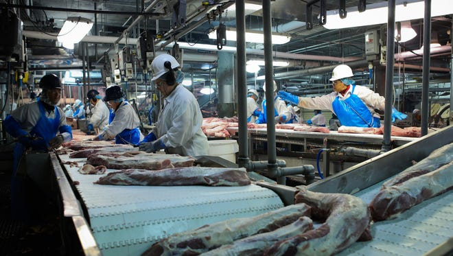 Pork products are prepared for shipment by various employees as it makes the way down conveyor belts inside Butchertown's JBS Swift  plant in Louisville earlier this year.