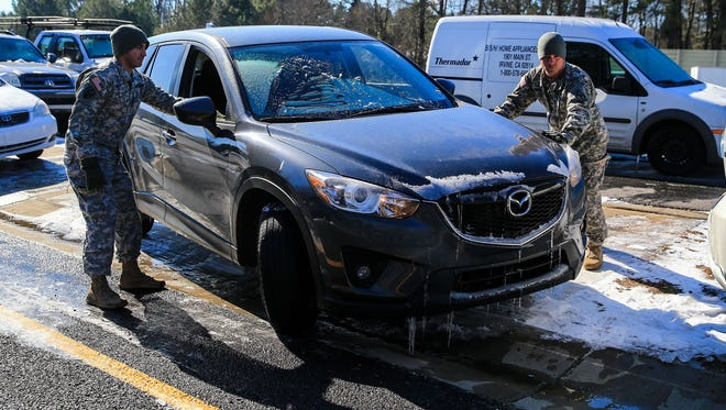 U.S. Army National Guard Ssgt. Anthony Orsi, left, and Ssgt. Raymond Novak help Lauren Gates retrieve her vehicle on the Cumberland Boulevard exit ramp on I-75 North on Jan. 30 in Atlanta.