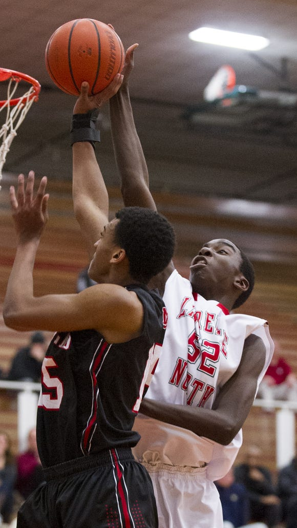 North Central High School sophomore T.J. Walton (25) is fouled by Lawrence North High School sophomore Ra Kpedi (52) as he tries to put up a shot during the first half of action. Lawrence North High School hosted North Central High School in a first-round game of the 2015 Marion County Boys Basketball Tournament, Tuesday, Jan. 13, 2015.