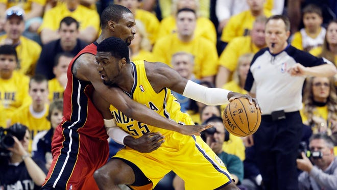 Indiana Pacers center Roy Hibbert, left, drives against Miami Heat center Chris Bosh during the first half of Game 1 of the Eastern Conference finals on Sunday.