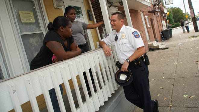 Lashell Hall and her 16-year-old daughter, Dashnany Howell, visit with Wilmington police officer Lt. Dan Selekman. Selekman was able to get the mother and daughter jobs at McDonald's.