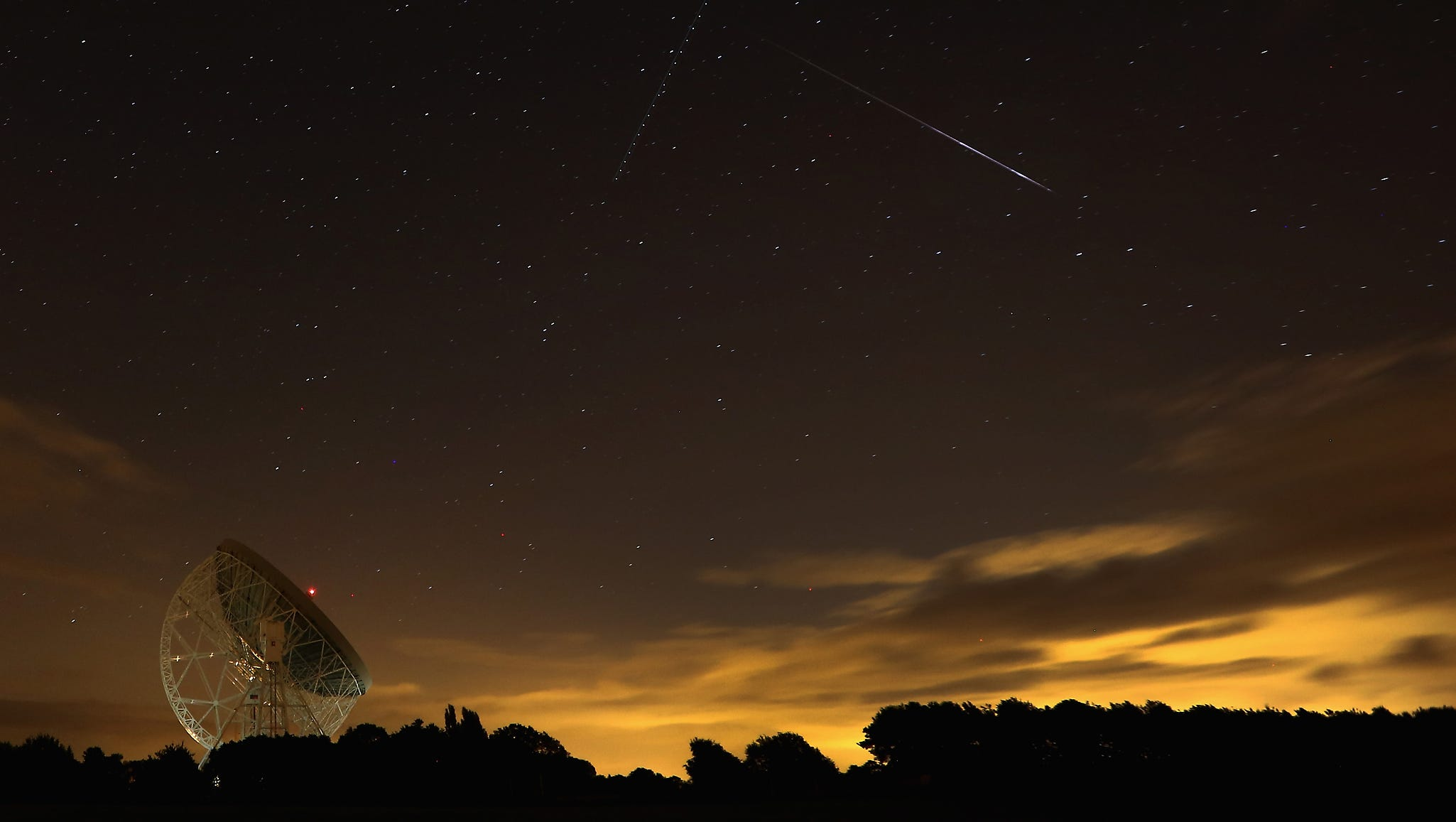 A meteor passes over the Lovell Radio Telescope at Jodrell Bank on Aug. 13 in Holmes Chapel, England.