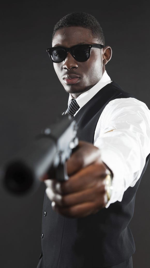 This is a photo illustration of a black American mafia gangster man in suit with gun.