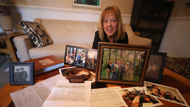 Jayne Gastineau with her birth certificate, a letter written by her birth mother and photos of her family members, many of whom she recently united with after learning the identity of her birth parents.