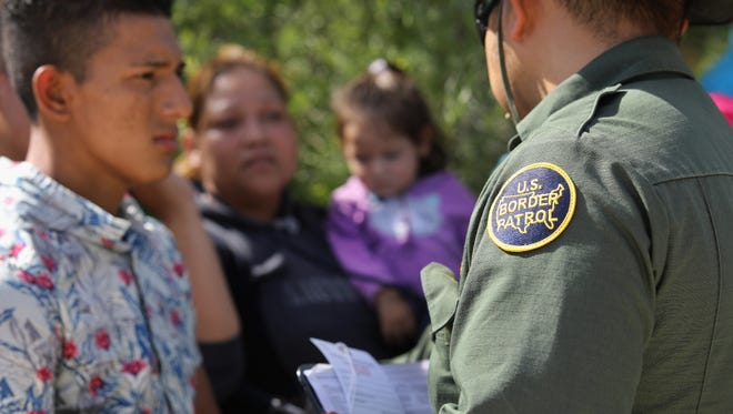 A U.S. Border Patrol agent takes a group of Central American asylum seekers into custody on June 12, 2018 near McAllen, Texas. The immigrant families were then sent to a U.S. Customs and Border Protection (CBP) processing center for possible separation.