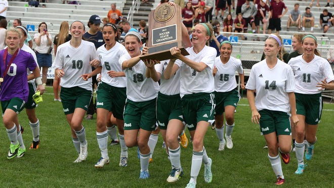 Members of the Iowa City West run their championship trophy to their fans after a 1-0 win over Dowling Catholic during the Iowa Class 3A state soccer championship match at Cownie Sports Complex in Des Moines on Saturday, June 13, 2015.