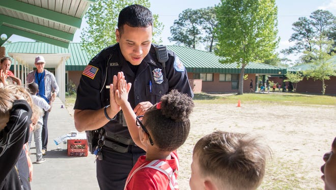 Off-duty Pensacola Police Department and school resource officer Michael Garcia high-fives students while walking around Scenic Heights Elementary School in Pensacola on Wednesday, April 18, 2018.