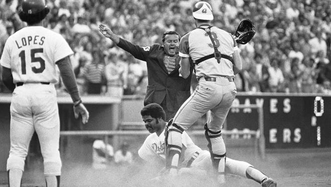 Home plate umpire Dutch Rennert calls Los Angeles Dodgers' Reggie Smith safe under Atlanta Braves catcher Dale Murphy (3) during a July 5, 1978, game in Los Angeles.