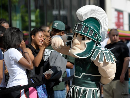 MSU mascot Sparty gives a high five to Kendall McConico,