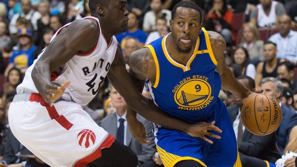 Golden State Warriors' Andre Iguodala, right, drives past Toronto Raptors' Pascal Siakam during the first half of a preseason NBA basketball game in Vancouver, British Columbia, Saturday Oct. 1, 2016. (Darryl Dyck/The Canadian Press via AP)