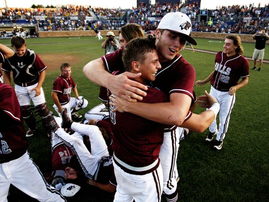 Menomonee Falls' Ty Weber, back, hugs Nick Gile (8) after defeating Marquette in the summer baseball state title game.