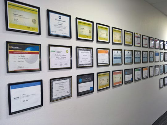 IQ Technology Solutions' wall of technical certifications.