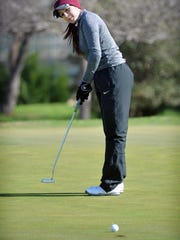 Sarah Moore watches a putt roll in while competing in the Midwestern State University Invitational golf tournament Monday morning at the Wichita Falls Country Club.