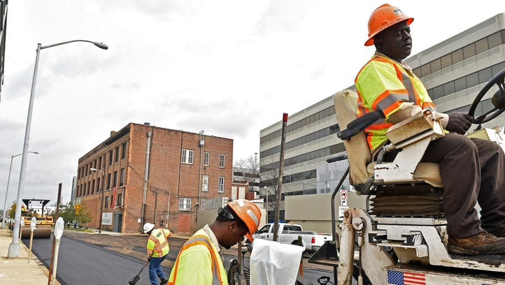 APAC Mississippi employee Rick Morton, right, drives a paver on a section of South Farish Street in downtown Jackson.