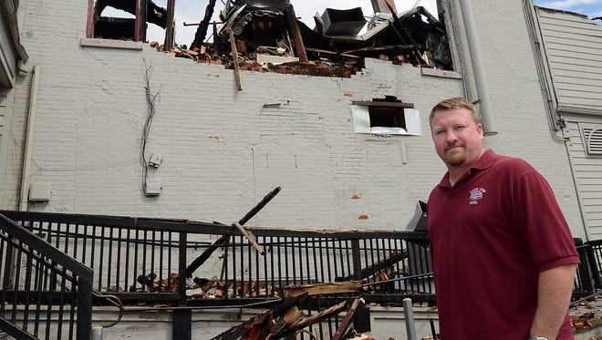 Corry Bala, an operating partner of the South Lyon Hotel, stands at its fire-damaged site last month.