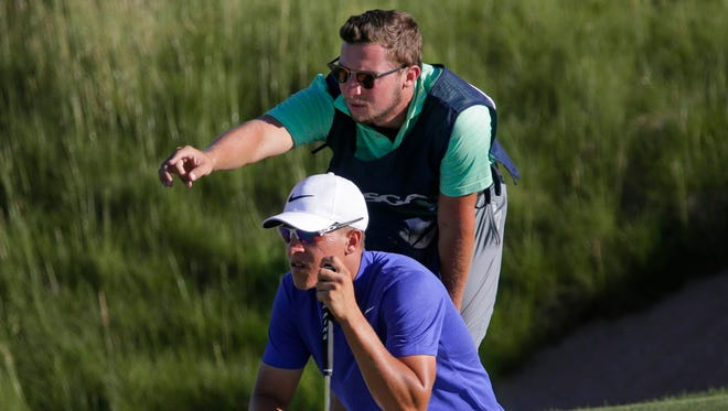 Amateur Cameron Champ consults his caddie Jake Goodman on a putt on No. 4 during the first round of the U.S. Open at Erin Hills.