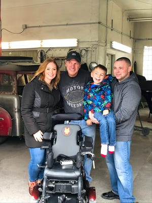 From left,  Nicole Ey, Jerry Fournier, Devin Ernst and Calvin Ernst pose with the wheelchair that Fournier, of R&J Auto Body and Repair in Port Jervis, painted in Iron Man style for Devin.
