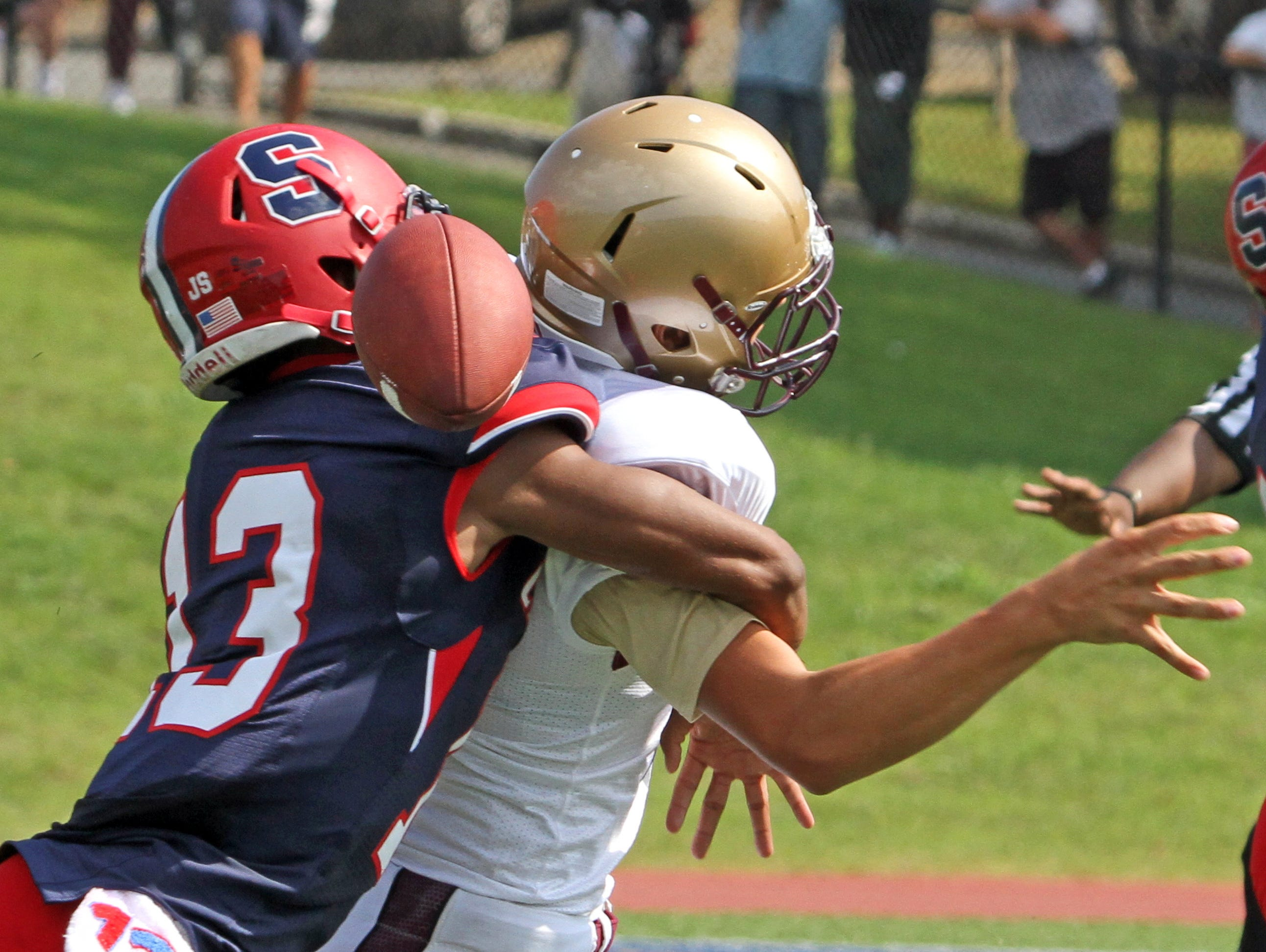 Stepinac's Devante Reid forces Iona Prep quarterback Michael Apostolopoulos to fumble during a varsity football game at Stepinac High School Sept. 19, 2015. Stepinac crushed Iona Prep 48-6.