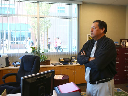 Rudy Ramirez looks at students outside of his office