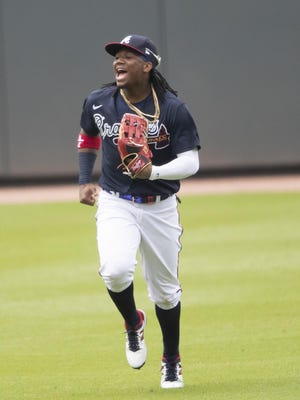 Atlanta Braves center fielder Ronald Acuna Jr. (13) jokes with teammates as he runs in from the outfield during a practice baseball game, Thursday, July 9, 2020, in Atlanta.