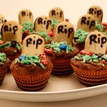 """For graveyard cupcakes, frost the cakes with rich chocolate ganache and decorate with cookie """"tombstones."""""""