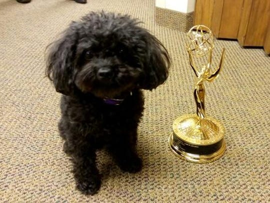 Nala poses with Boyd Huppert's Emmy statue, which he
