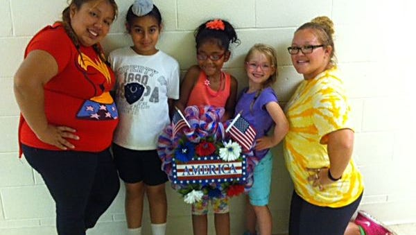 """Writing letters to military personnel was one of the activities campers participated in during the YMCA of Vineland's """"Super Heroes"""" week for children ages 6 to 8. (From left) Alicia Pedro-Martin, lead counselor at Camp Hiawatha, who suggested the idea, is pictured with campers Jagnoor Singh, Lisette Trujillo and Summer Morello; and Ashley Parent, camp director."""