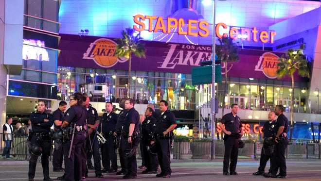 Los Angeles police officers stand in front of Staples Center following a  Lakers-Grizzlies game on Nov. 26. Several people who were protesting the Ferguson, Mo., grand jury decision marched in front of the arena after the game ended.