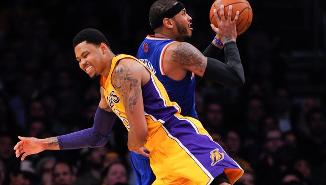New York Knicks forward Carmelo Anthony (7) is fouled as he shoots by Los Angeles Lakers guard Kent Bazemore (6) during the second half at Staples Center.