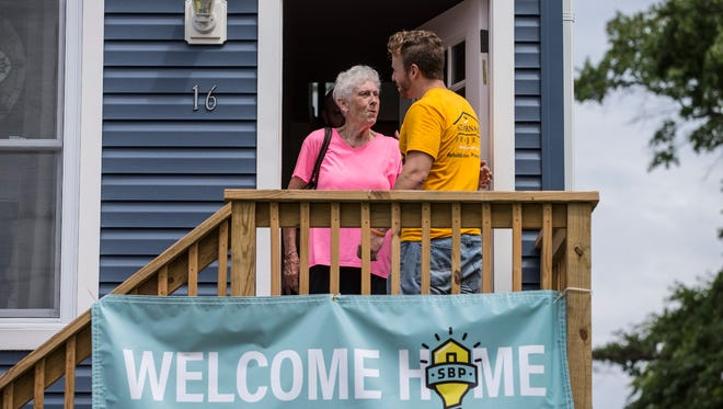 After years of waiting, Pat Kenny is able to move into a home that has been rebuilt after Hurricane Sandy destroyed her former dwelling. She was a victim of contractor fraud and only got the project complete thanks to volunteers from SBP New Jersey. Kenny walks out of her new front door with Mark Smith, volunteer department manager of SBP New Jersey.