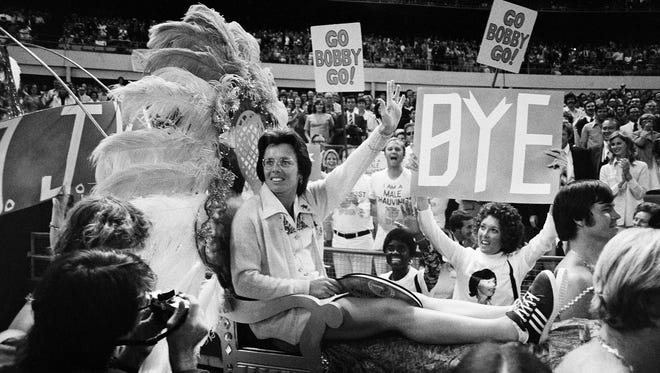 Billie Jean King sits on a throne carried by four men for her match with Bobby Riggs.