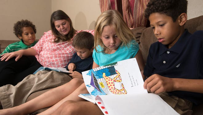 Jessie Howell, second from the left, looks on with her adopted foster son, Everett, left, and as her biological child Ezekiel, reads while her other adopted foster child, Ellis, far right, teaches her other child, Zula, right center, to read. The Howell's have been foster care providers for three years.