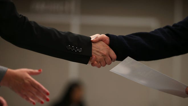 A job seeker shakes hands with a recruiter during a HireLive career fair on June 4, 2015 in San Francisco, California. According to a report by payroll processor ADP,  201,000 jobs were added by businesses in May.  (Photo by Justin Sullivan/Getty Images)