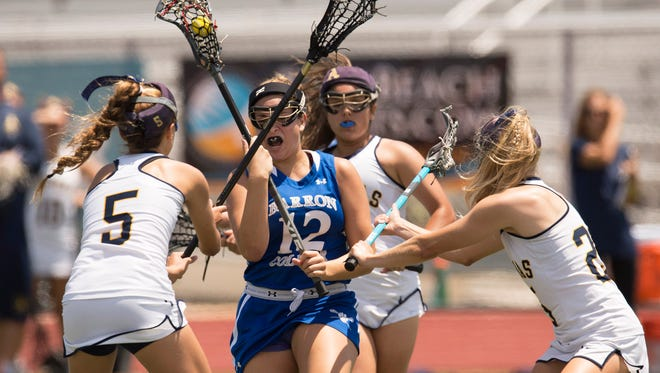 Barron Collier's Jaclyn Berry (center) brings the ball upfield as St. Thomas Aquinas' Kaitlyn Michaud (left) and Aryal Fette apply defensive pressure in the first half of their semifinal game during the FHSAA Lacrosse State Championships at Jupiter High School Friday, April 28, 2017. Barron Collier lost 9-12.