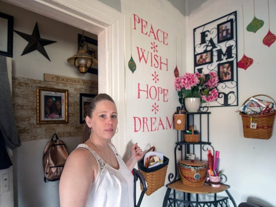 "Christine Bowie, Zach Swoyer's mother, with a mural her daughter painted in the living room that says "" Peace, Wish, Hope, Dream"""