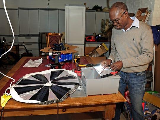 Mawuli Tse works on a portable solar unit at his workshop in Nashville.