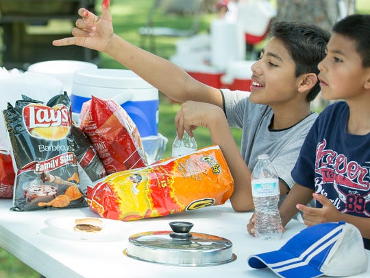 Iglesia Evangelica members Derek Valdez (left), 10, Gabriel Gomez, 13, and Ethan Mora, 6, check out a bird at Young Park as they enjoy a Fourth of July barbecue with family and friends.