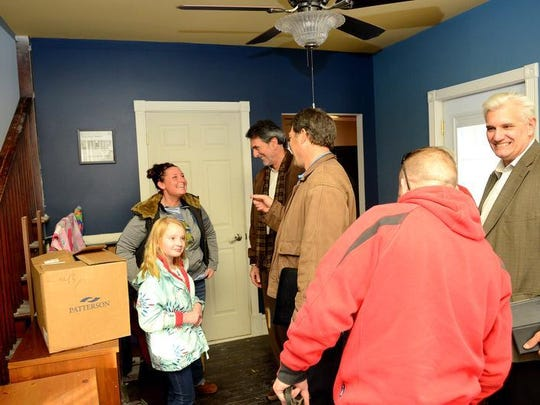 Melanie Newcombe and daughter Teegan, 9, talk with members of Faith Works and Operation: Come H.O.M.E. in their house in Ionia on Tuesday. Newcombe's husband Brandon, a Marine, bought the house for the family to fix up and live in. Brandon died on May 16, 2014, but the two Michigan non profits teamed up to finish the work on the house.