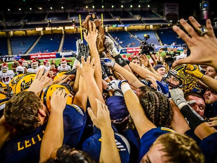 Members of the Ithaca football team lift the Division 6 state championship trophy after their come from behind win over Clinton Friday November 27, 2015 at Ford Field in Detroit.
