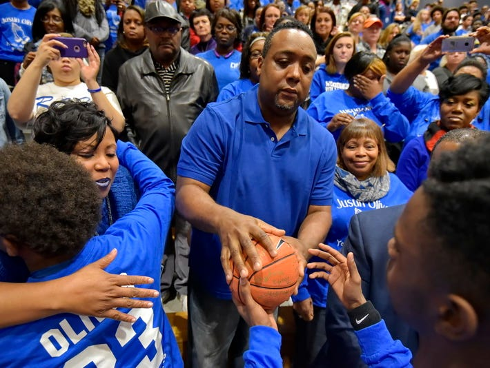Stacey Oliver, mother of the late Justin Oliver, gets a hug from a Woodmont basketball player Tuesday night as another player presents a ball signed by the team to Larry Oliver, Justin's father, before Woodmont's game against Mauldin.