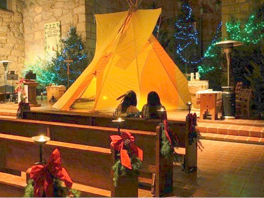Two Mescalero Apache maidens are silhouetted against the teepee protecting the creche on Christmas Eve.