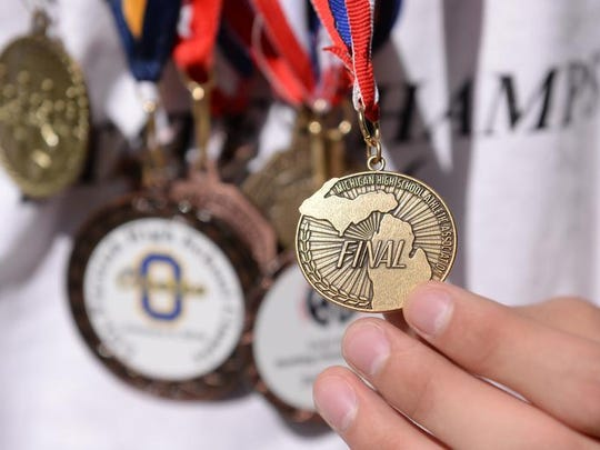 Victor Riojas holds one of his bowling medals on Friday in Lansing. Riojas is a member of the state champion Eastern High School Bowling Team.