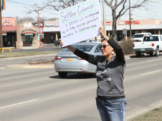 Kirtland resident Tisa Russell displays a sign for motorists on East Main Street Saturday during a rally welcoming immigrants to America on the grounds of the Farmington Museum at Gateway Park.