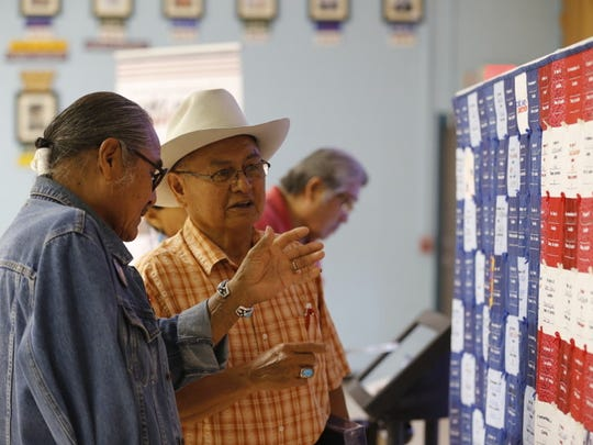 """Shiprock Chapter President Duane """"Chili""""' Yazzie, left, and Gadii'ahi Chapter resident Bobby Charley look at the remembrance quilt that honors former nuclear weapons and uranium mine workers that was displayed on Thursday in Shiprock."""