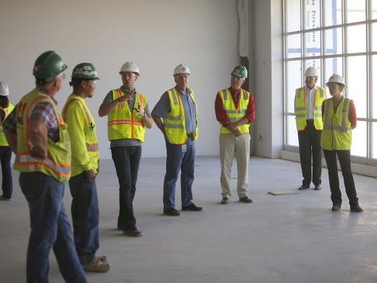 Jeremy Trumble, third from left, of FBT Architects, describes a feature of the new Farmington High School Library to district officials during a tour of the facilities on Thursday.