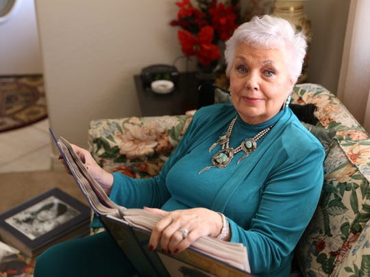 Sallyanne Bachman looks through one of the scrapbooks chronicling her long career as a musical theater and opera star at her Farmington home on Friday.