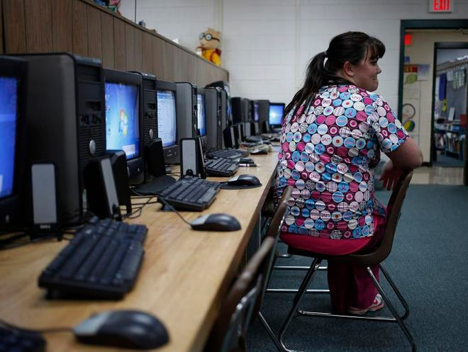 """Courtney Lively, a navigator for Kentucky's health care exchange waits for people to show up during an Affordable Care Act enrollment event at Highland-Turner Elementary School on Nov. 20 in Owsley. Asked to describe Breathitt County, Lively paused for a moment and then said: """"Poor. Just poor.""""  photos by Luke Sharrett/The Washington Post"""