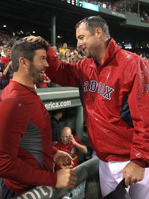 Tim Wakefield, right, of the Boston Red Sox reacts with teammate Jason Varitek after earning his 200th win in 2011.